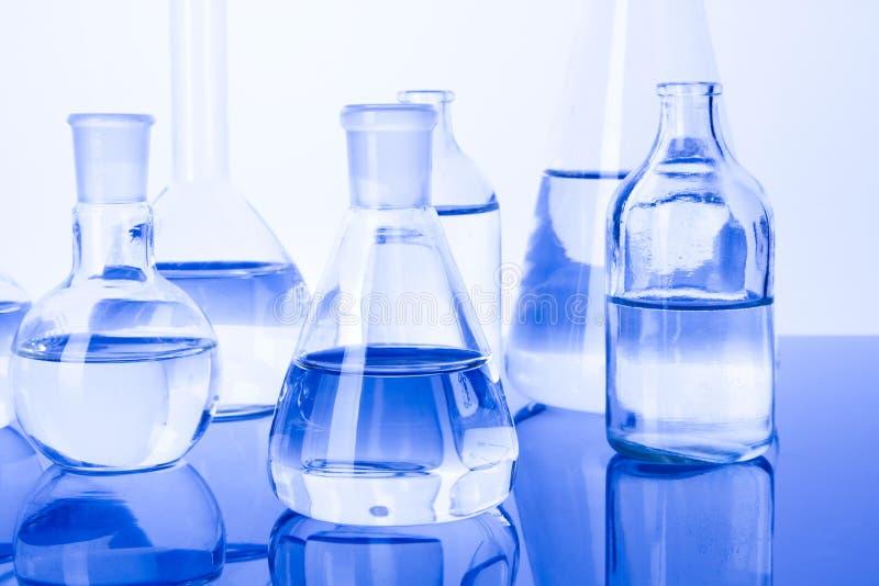 Cristalería de laboratorio en fondo azul imágenes de archivo libres de regalías