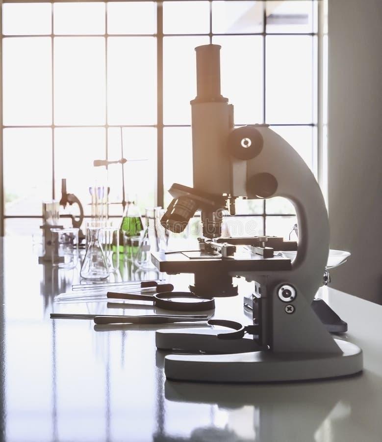 Cristalería de los microscopios y de laboratorio en la tabla en el laboratorio junto con los diversos accesorios que es pronto pa foto de archivo libre de regalías