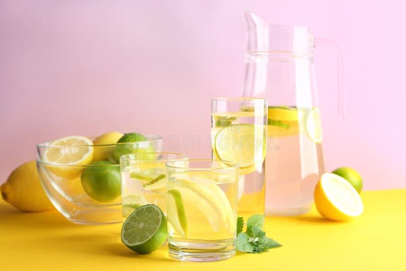 Cristalería del agua con el limón y la cal en la tabla de color fotografía de archivo libre de regalías