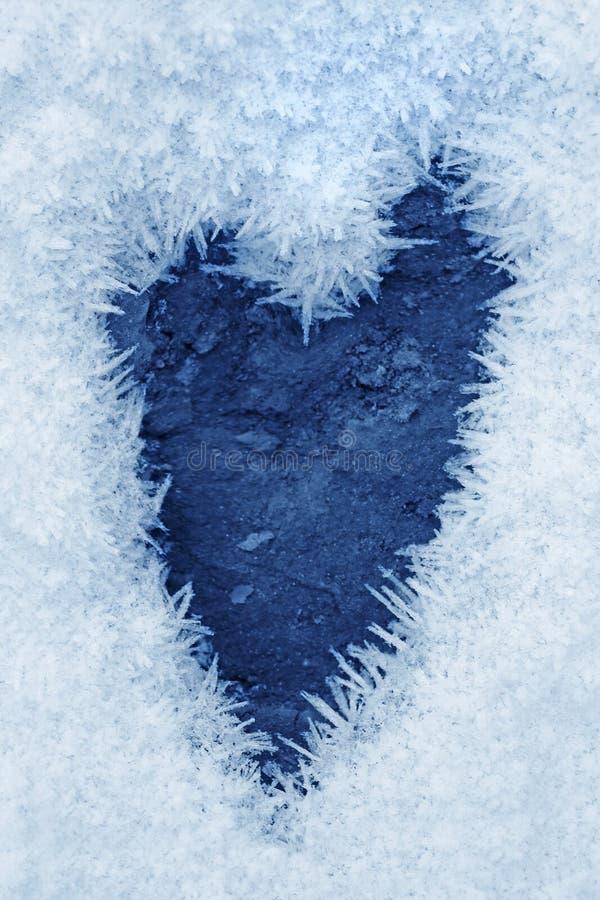 Cristales de hielo congelados en la tierra una forma del corazón imagen de archivo
