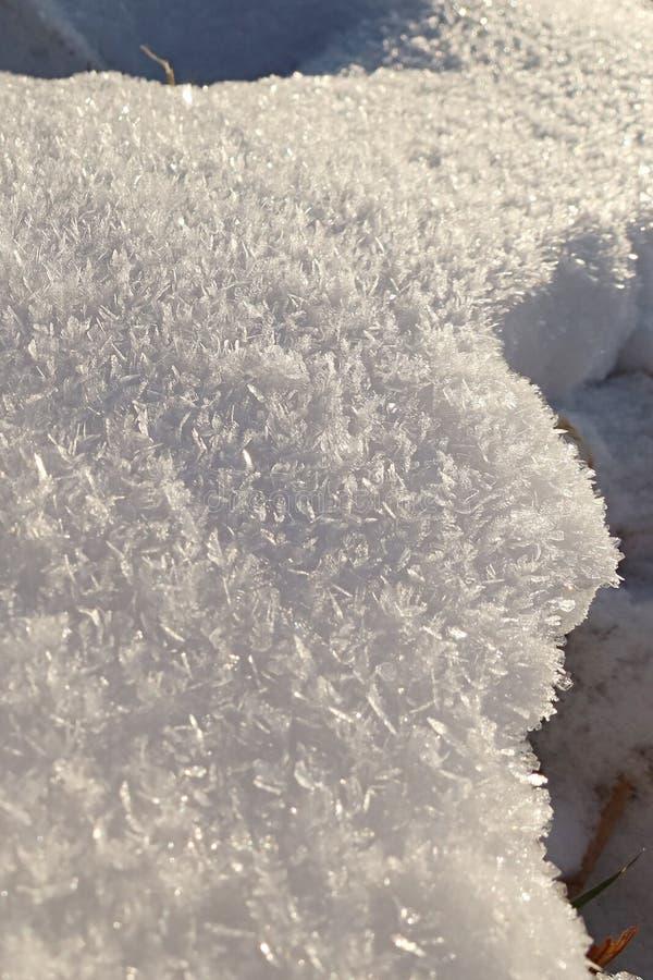 Cristales de nieve cerca del agujero creado por el camino de los pies fotos de archivo