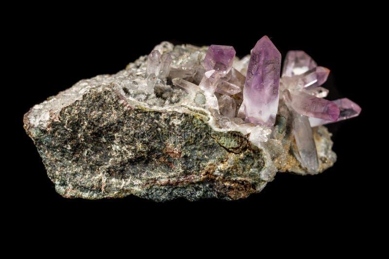 Cristales de piedra minerales macros de la amatista en roca en un fondo negro foto de archivo libre de regalías