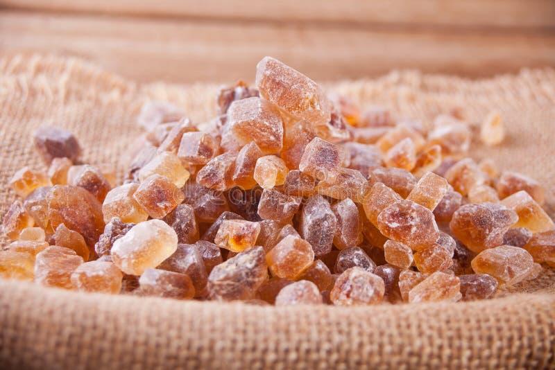 Cristalino orgánico de la roca del azúcar de Brown en una servilleta del yute fotos de archivo libres de regalías