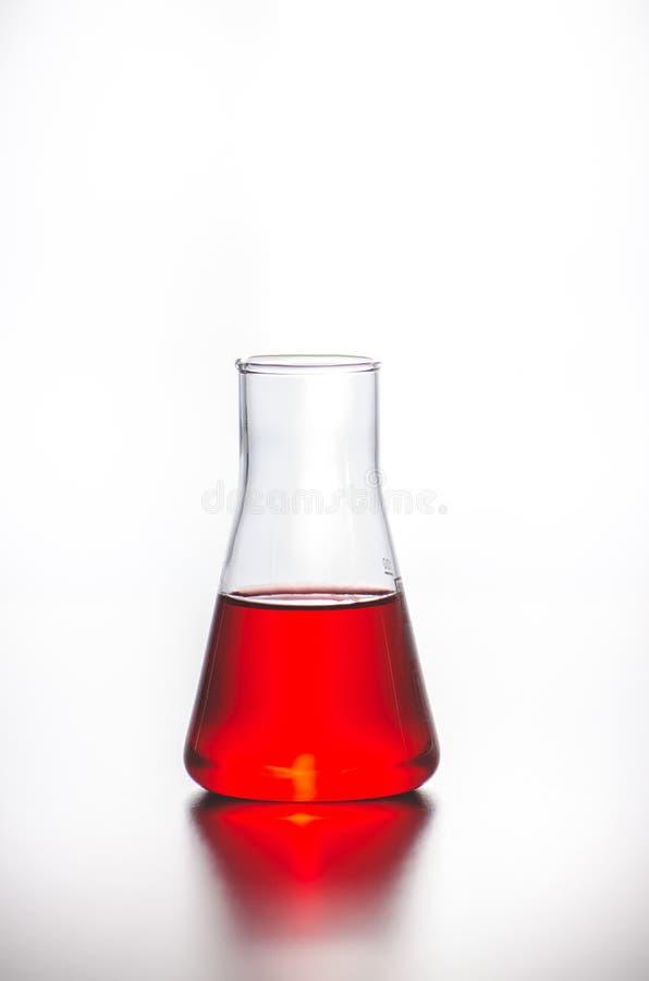 cristalleria Boccetta con liquido rosso su un fondo bianco Prove di laboratorio immagine stock libera da diritti