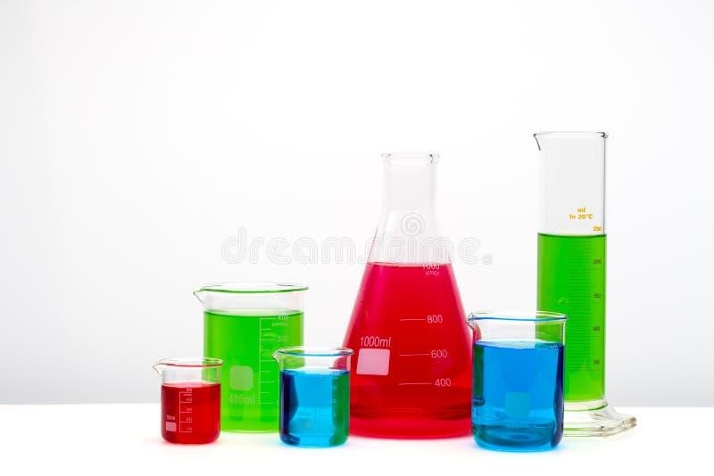Cristalleria riempita di liquidi verdi, blu e rossi Attrezzatura di laboratorio su fondo bianco immagini stock libere da diritti