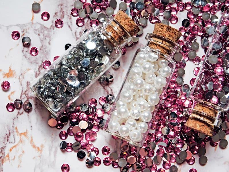Cristalli di rocca d'argento e rosa e perle bianche in barattoli di vetro con i coperchi di legno su un fondo di marmo fotografie stock