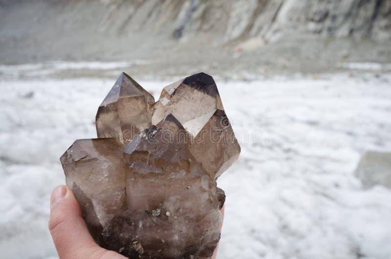 Cristalllier que sostiene cristales de cuarzo ahumado imágenes de archivo libres de regalías
