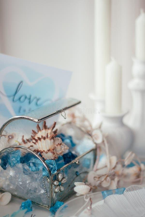 Cristaux de coquilles, bleus et blancs dans une boîte en verre, bougies images libres de droits