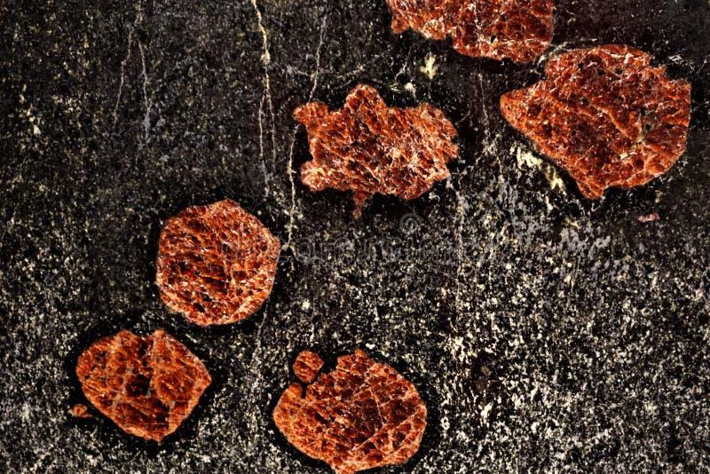 Cristaux rouges abstraits dans la roche noire photo libre de droits