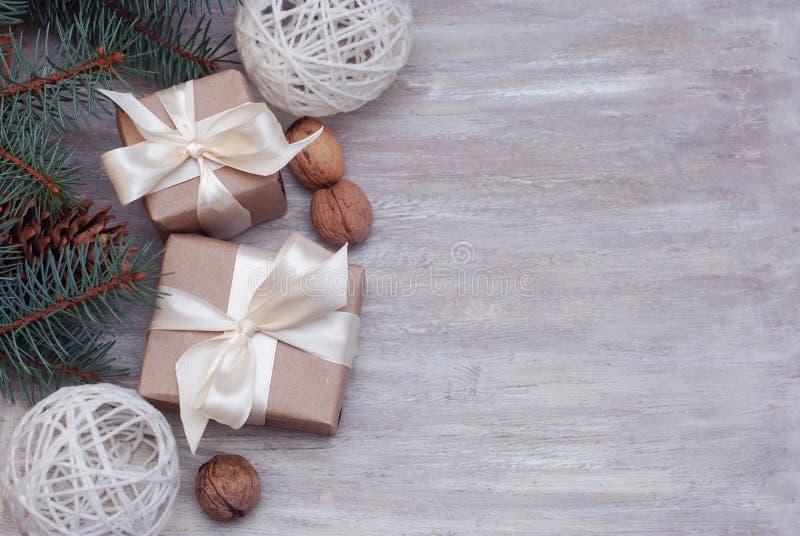 Cristmas礼物礼物布朗箱子与,冷杉分支,坚果,在与拷贝空间的木背景文本的 免版税图库摄影
