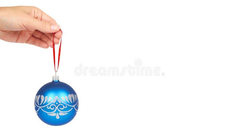 Cristmas装饰,在白色背景在手中隔绝的玻璃蓝色球 新年对象 复制空间,模板 免版税库存图片