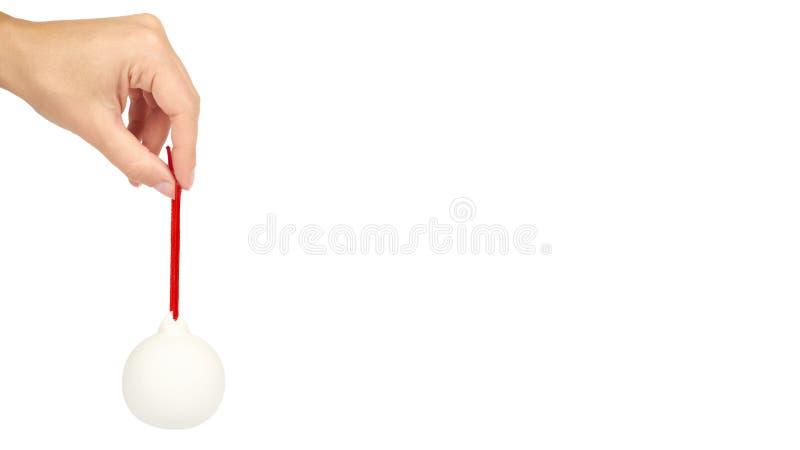 Cristmas装饰,在白色背景在手中隔绝的玻璃陶瓷白色球 新年对象 复制空间,模板 免版税图库摄影