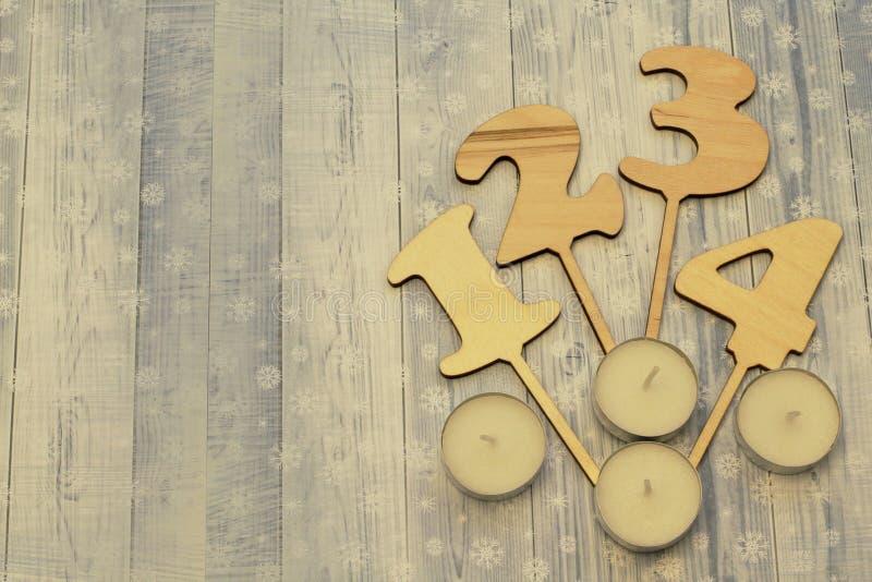 Cristmas allegro avvenimento Numeri e candele di legno casalinghi su fondo leggero con i fiocchi di neve fotografie stock libere da diritti