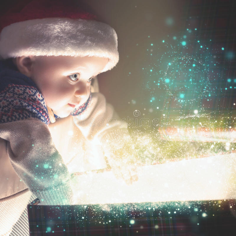 Cristmas baby holding gift with abstract fairy dust, stardust. Christmas. Cristmas infant holding gift with abstract fairy blowing fairy magical dust, stardust stock photo