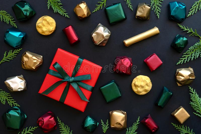 Cristmas background with gift box and colorful wrapped chocolate candy. Top view royalty free stock image