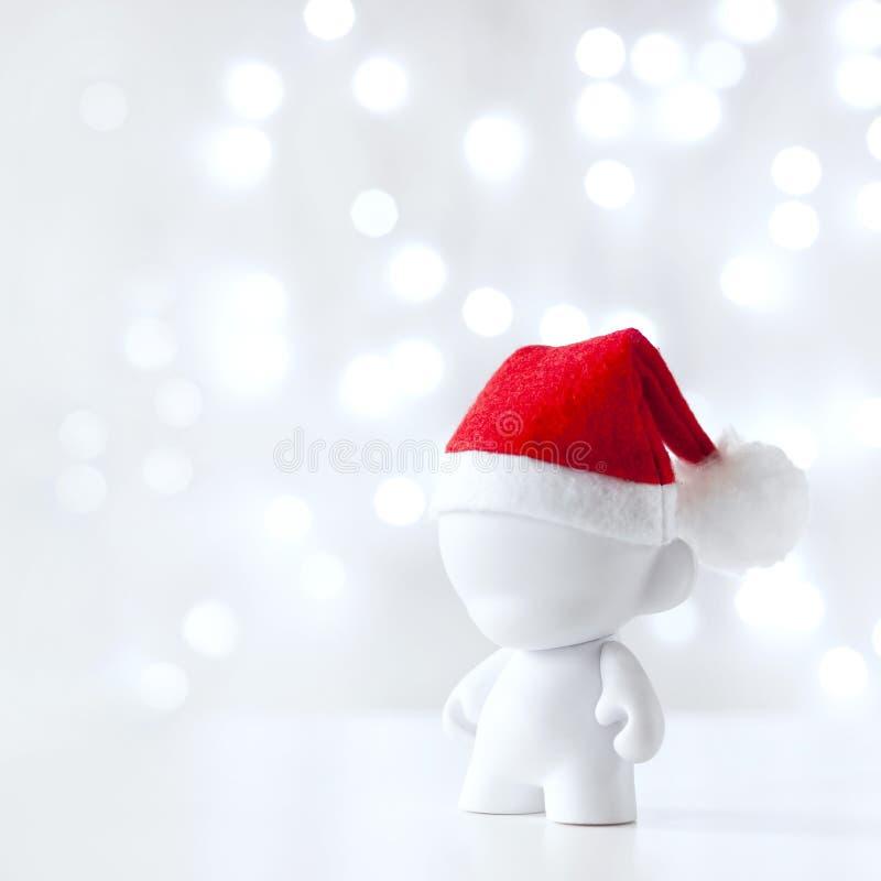 Cristmas-Spielzeug in Red Hat Santa Claus, Symbol-neues Jahr, Defocused Licht-Weiß-Hintergrund stockfoto