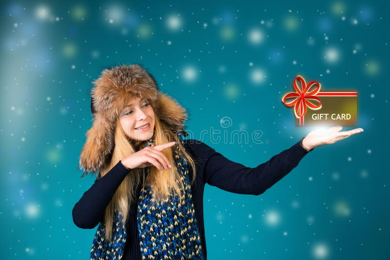 Cristmass gift card. Winter woman is pointing showing a gift card. royalty free stock image