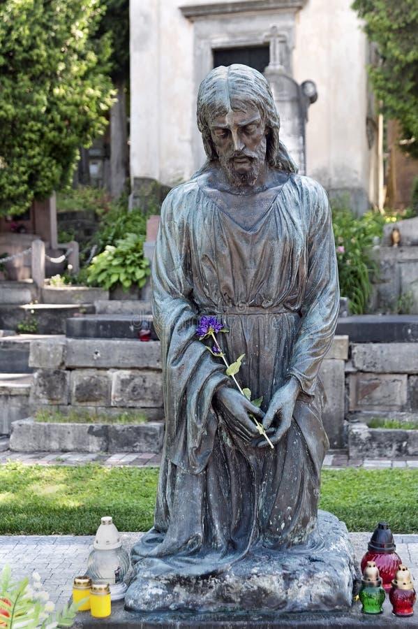 Cristo na lápide dobrada dos joelhos no cemitério de Lychakiv em Lviv Ucrânia imagens de stock royalty free