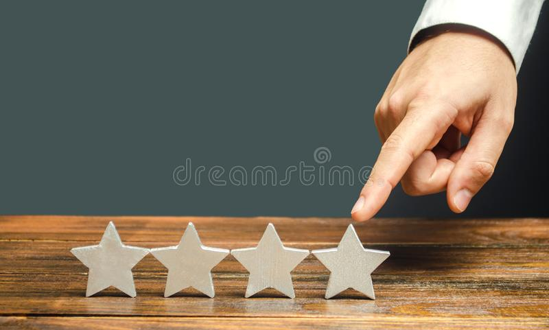 Critic puts the fourth star. The concept of the rating of hotels and restaurants. The evaluation of visitors. Quality level, good. Service. Customer rating royalty free stock image
