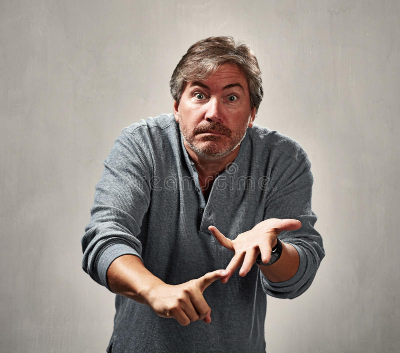 Critical angry man. Critical blaming man portrait over gray wall background stock photography