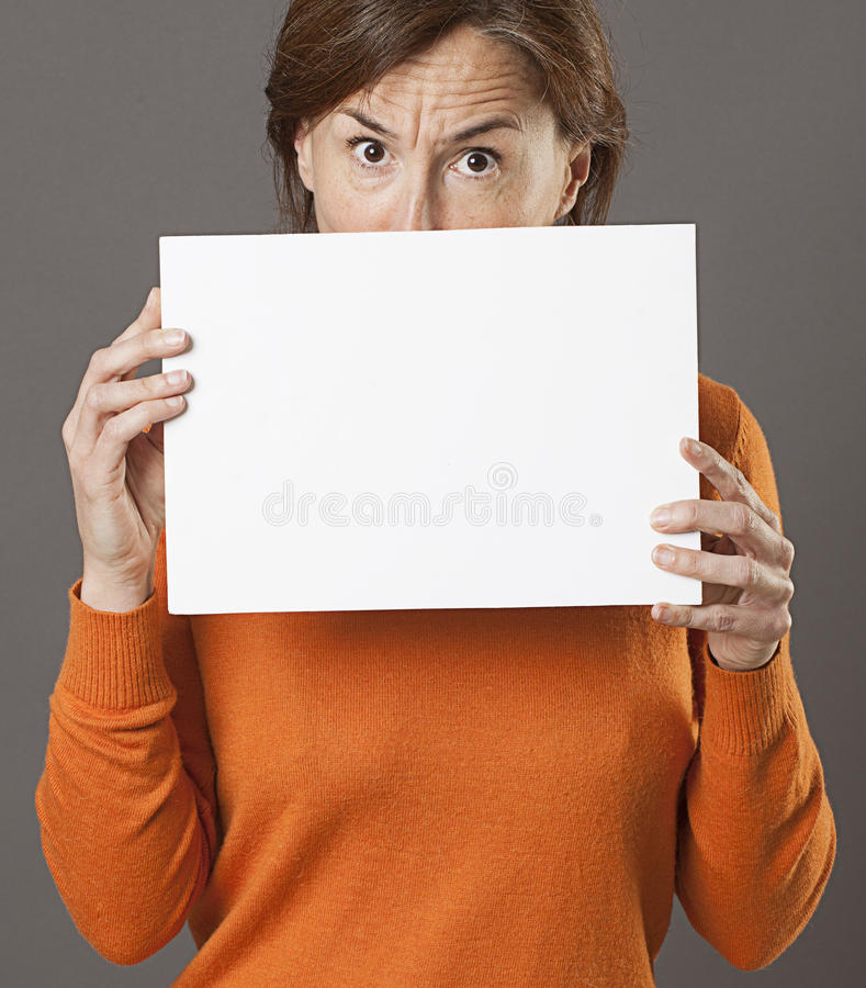 Critical middle aged woman hiding behind scary blank communication board royalty free stock photos