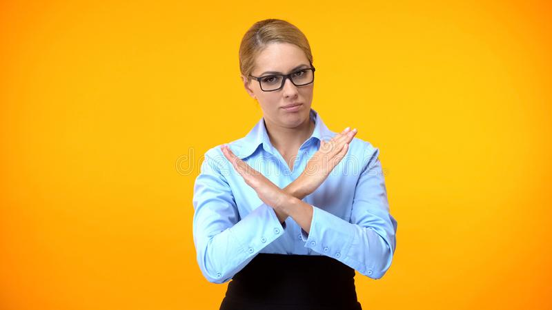 Critical office worker with crossed arms showing stop sign, business restriction stock photos