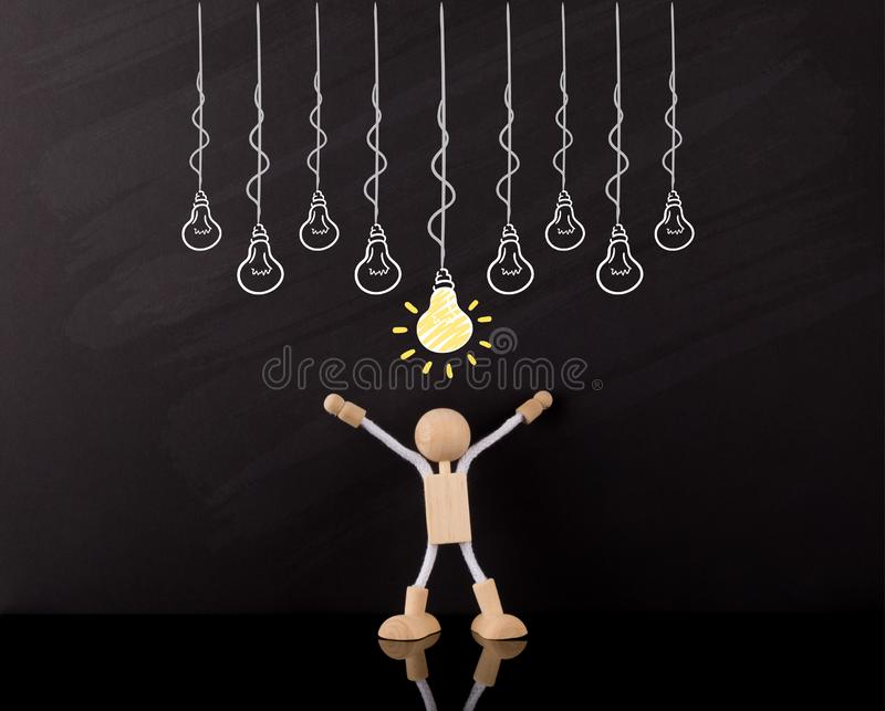 Critical Thinking Skills Concept, Wooden Stick Figure arms up, Big Yellow light bulb sketch, on a chalkboard stock photo