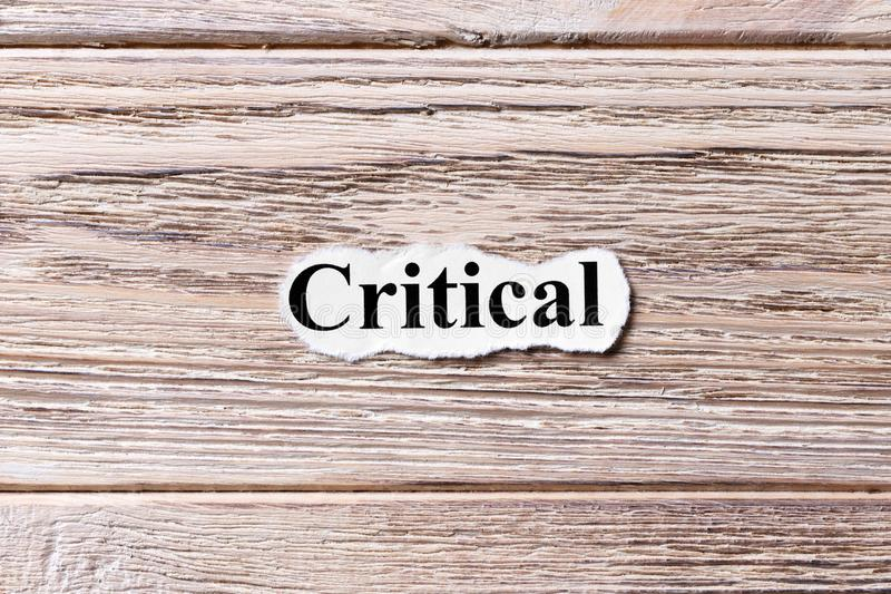 CRITICAL of the word on paper. concept. Words of CRITICAL on a wooden background.  stock photos