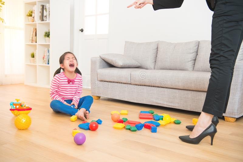 Criticize the sadness asian kid girl. Business women back from office and see her daughter play toys messy up the living room feel angry and criticize the stock image