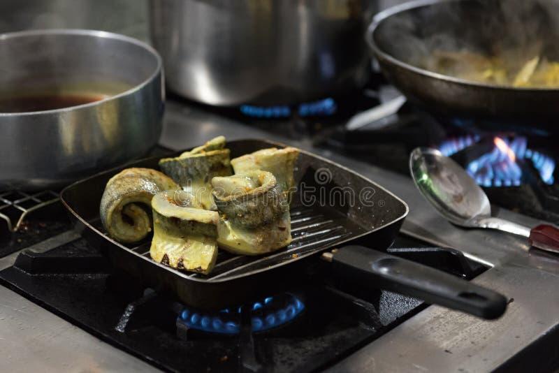 Critique los pescados de espada marchitos en una cacerola caliente con la llama del mechero de gas imagen de archivo libre de regalías