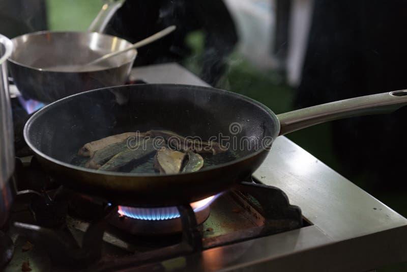 Critique los pescados marchitos en una cacerola caliente con la llama del mechero de gas imagen de archivo libre de regalías