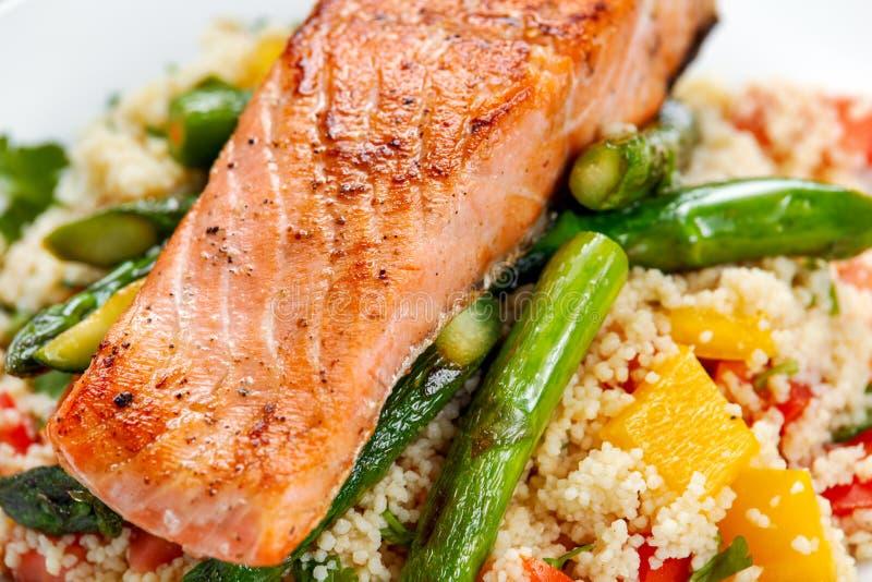 Critique los salmones fritos con el espárrago blando y el calabacín servidos en el cuscús mezclado con el tomate dulce, salsa ama imágenes de archivo libres de regalías