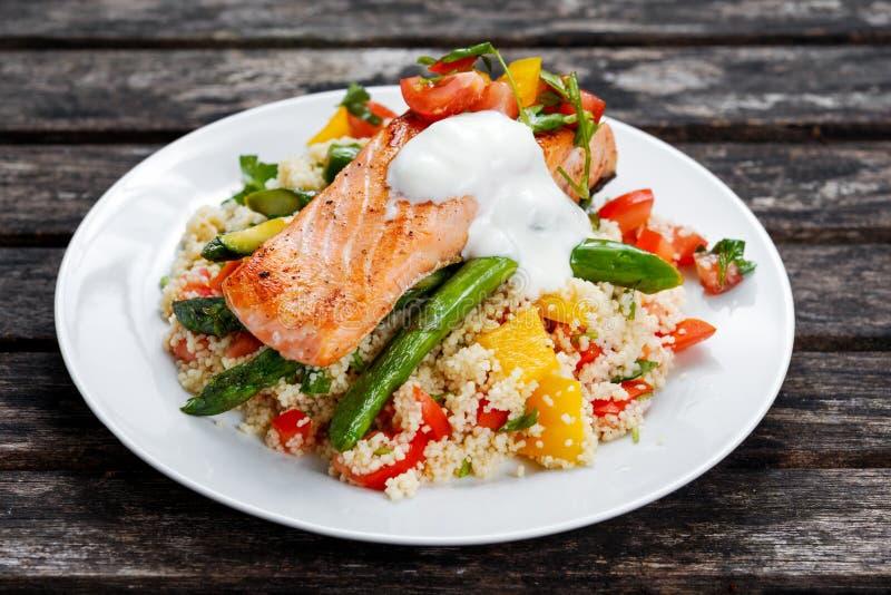 Critique los salmones fritos con el espárrago, el cuscús y las verduras blandos foto de archivo