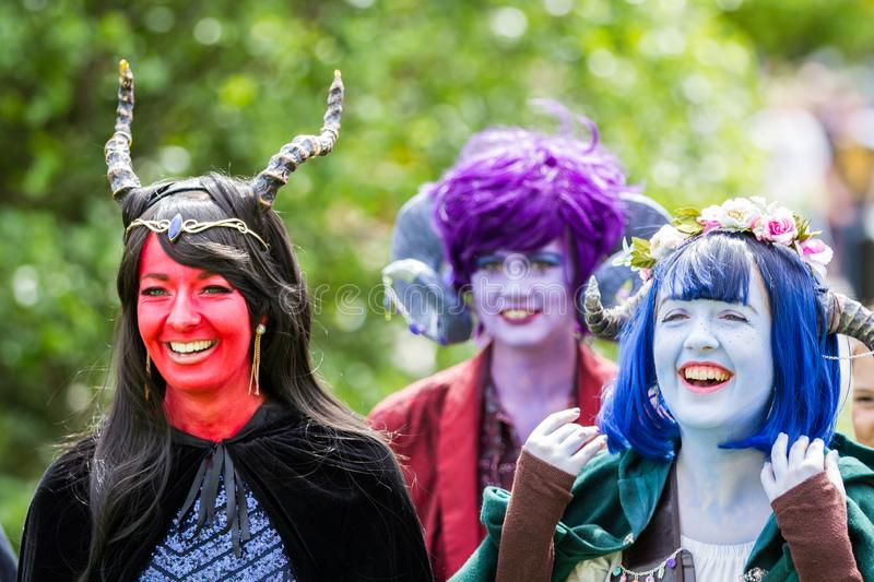 Critter Cosplayers laughing in colourful make up. NEC, BIRMINGHAM, UK - JUNE 1, 2019. Cosplayers dressed as colourful critters at a comic con event smiling and stock photography