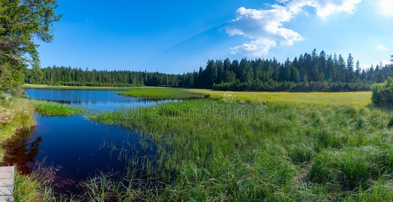 Crno jezero or Black lake, a popular hiking destination on Pohorje, Slovenia. Lake on top of mountain, dark colored water and vibrant green grass, surrounded stock photography