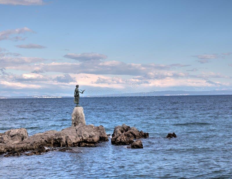 Croácia: Escultura de bronze/estátua da donzela com a gaivota no fundo um mar em Opatija foto de stock royalty free