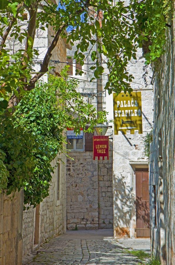 Croácia, Trogir - a rua velha da cidade com hotel assina imagens de stock royalty free