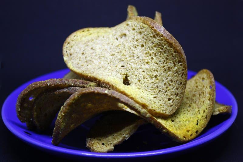 Croûtons de pain noir, dans les morceaux entiers empilés sur l'un l'autre d'un plat bleu, fond foncé, en gros plan image libre de droits
