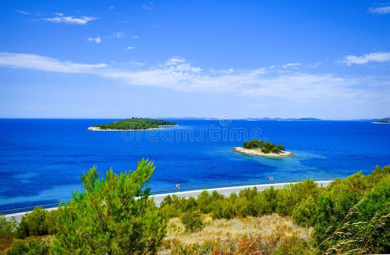 Croacia - mar azul y pequeñas islas con el camino a lo largo del distrito de Sibenik de la opinión panorámica de la costa A del m imagen de archivo
