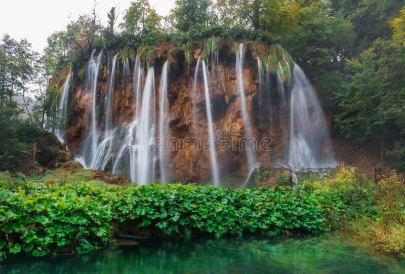 croatia Plitvice lakes Vattenfall i molnigt väder som omges av gröna växter royaltyfri foto
