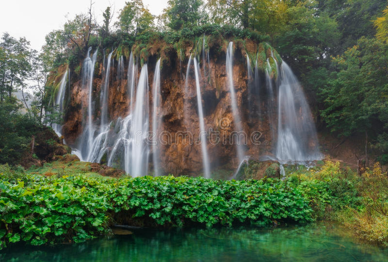 Croatia. Plitvice Lakes. Waterfall in cloudy weather, surrounded by green plants. Plitvice Lakes National Park, since 1979 are in the register of UNESCO World royalty free stock photo