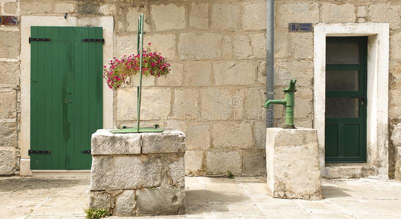 Croatia, summer landscape: a courtyard of an old stone Dalmatian bastion with a well and a water column stock images