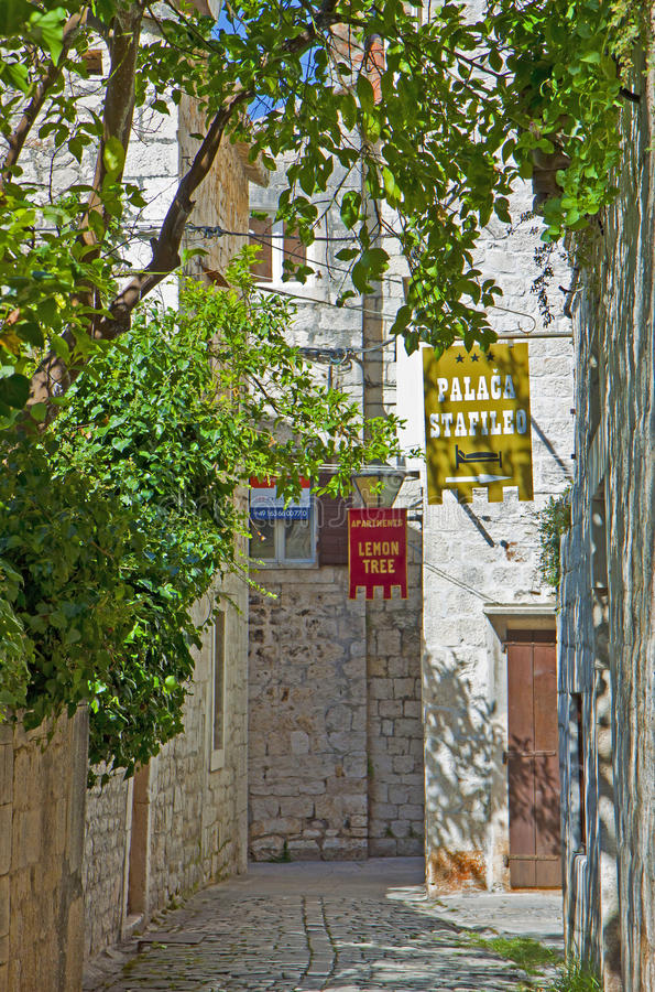 Croatia, Trogir - old town street with hotel signs. CROATIA, TROGIR - AUGUST 15, 2014. Along a medieval street in Trogir old town paved with cobblestones, signs royalty free stock images