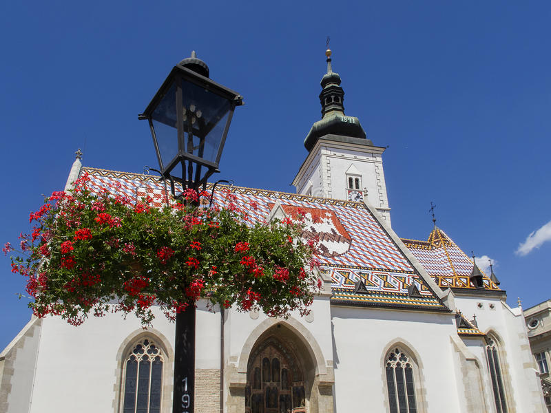 Croatian Church of St. Mark in Zagreb with beautiful red flowers on a Gas Lantern in front stock photos
