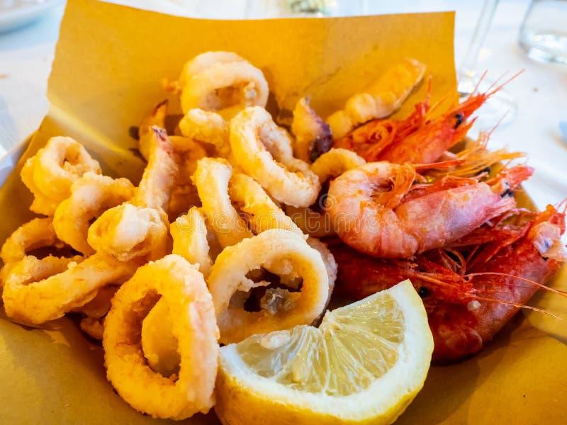 Croccanti di fritti di gamberi dei calamari e con il limone immagini stock libere da diritti
