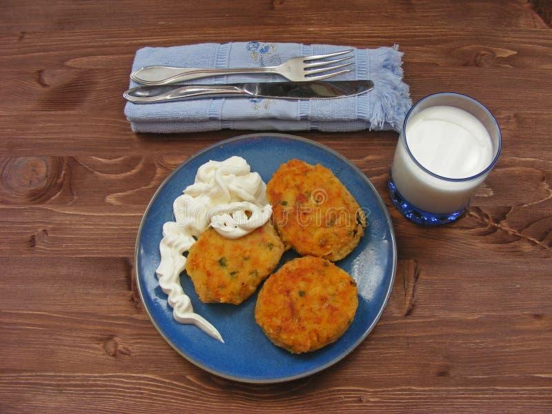 Crocchette del prosciutto, formaggio e patate sul piatto blu, latte in vetro e panna acida in ciotola di legno su fondo rustico c fotografia stock libera da diritti