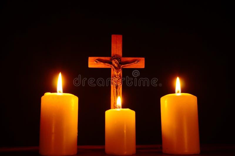 Croce e tre candele brucianti nell'oscurità Preghi a Jesu fotografie stock libere da diritti