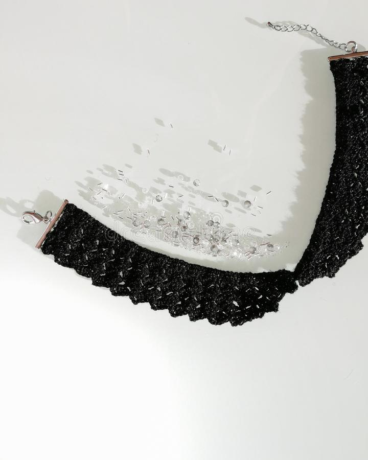 Crochet black necklace. Decorative lace collar with clasp. Mix of pearls and beads. royalty free stock photo
