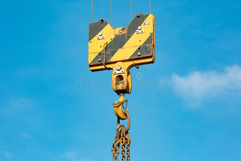 Crochet de charge de grue contre le ciel avec les traînées et la chaîne photographie stock