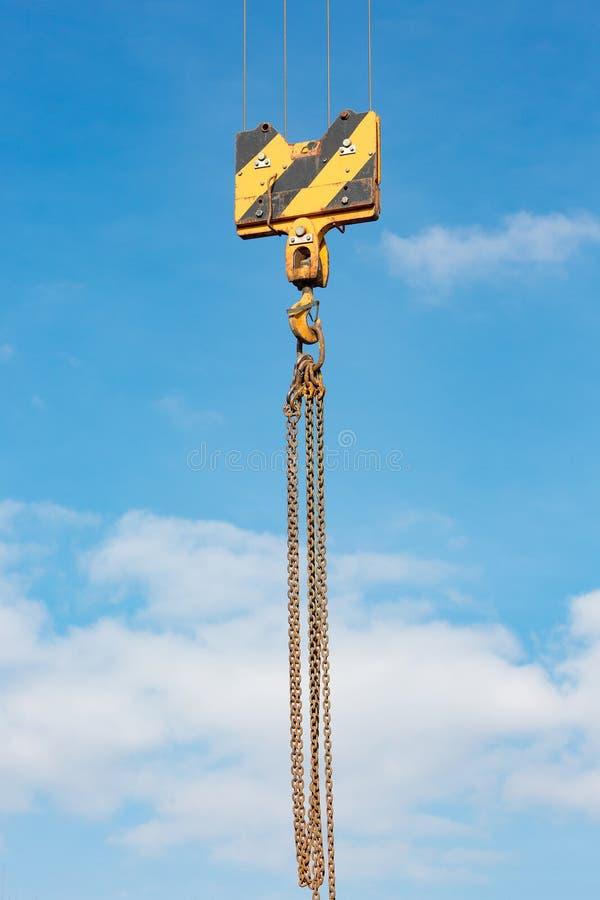 Crochet de charge de grue contre le ciel avec les traînées et la chaîne photo stock